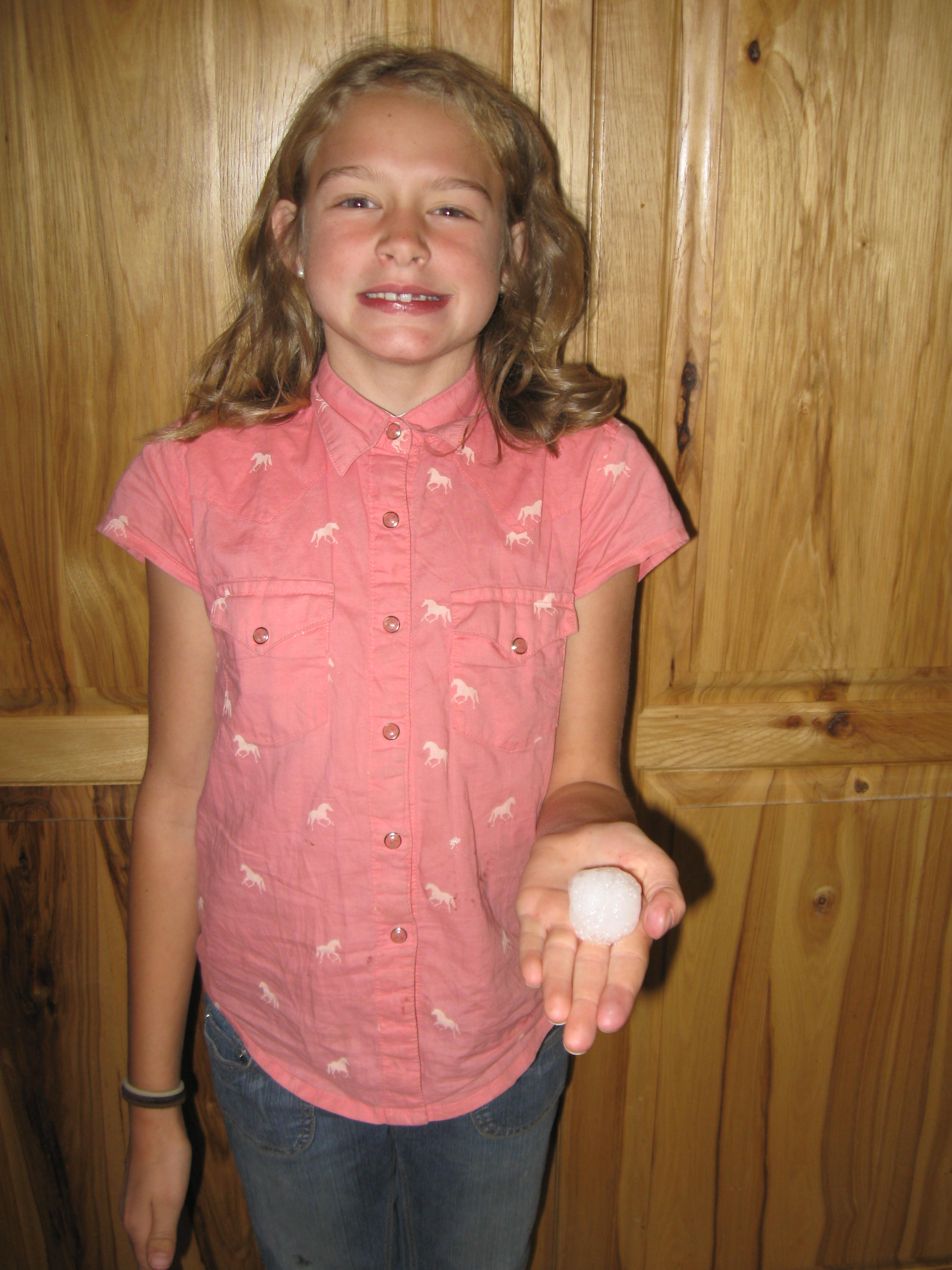 Our neighbor's daughter holding a hail stone