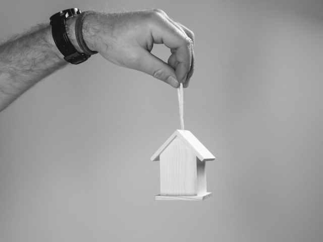 person holding miniature wooden bird house