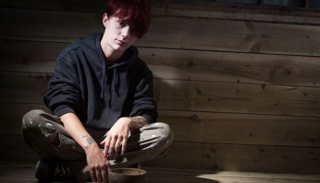 Young homeless lad sitting on floor