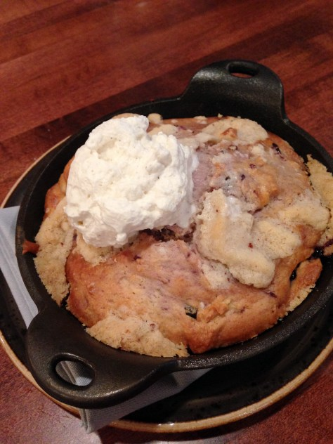 Ellen's Berry Buckle cooked in a cast iron pan creates the perfect ratio of caramelized crust and rich soft middle.  Topped with cream you