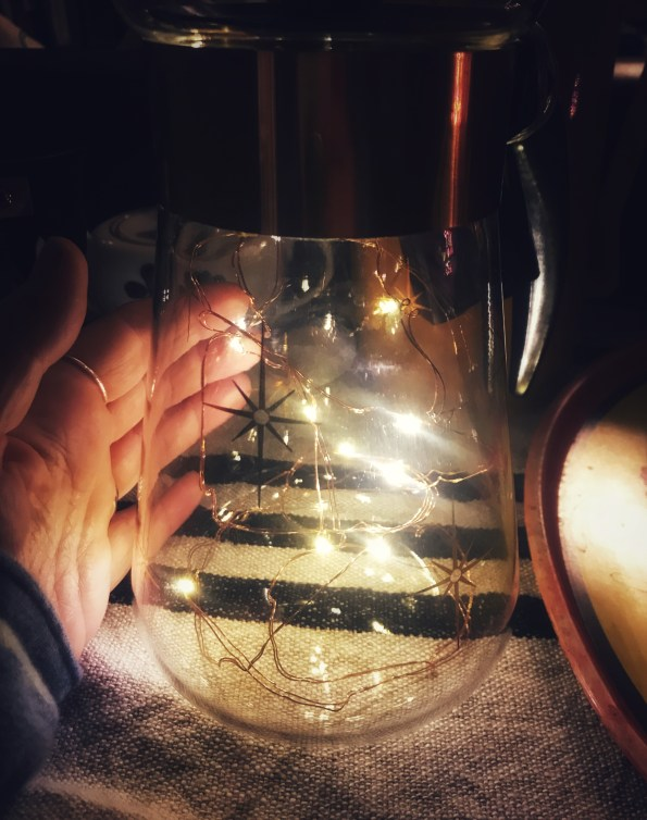 holiday lights in a vintage coffee carafe