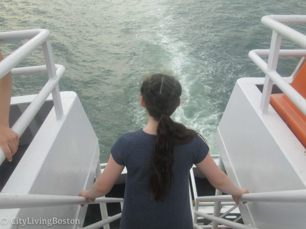Isabelle on a boat looking back at the wake.