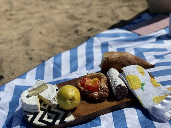 cheese and bread on a picnic blanket at the beach