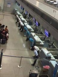 Uslužbenci na letališču se opravičujejo potnikom zaradi leta, ki zamuja.
