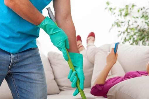 Mann som vasker mens kvinne ligger på sofa