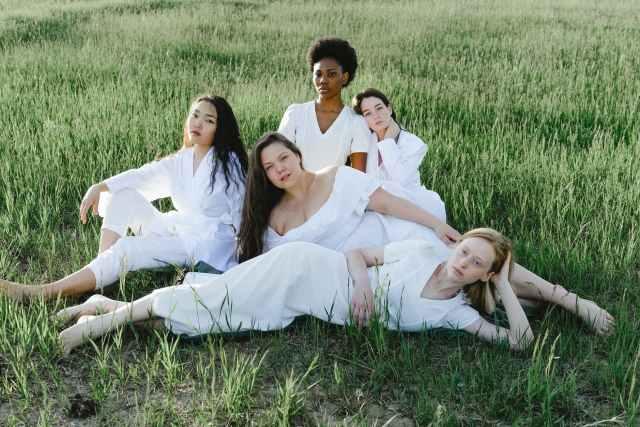 group of women lying on green grass field