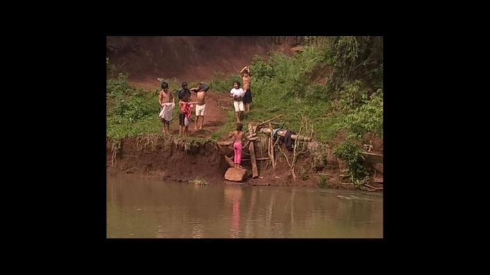 Chicos misioneros cruzan nadando un arroyo para ir a la escuela.