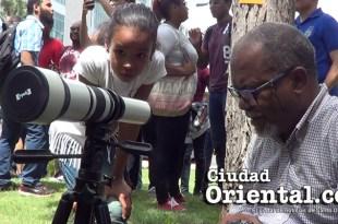 Una niña observa a Genris García mientras prepara su equipo pata fotografiar el eclipse.