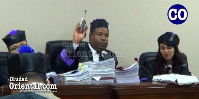 El juez Eduardo De los Santos, presenta el revólver para su acreditación.