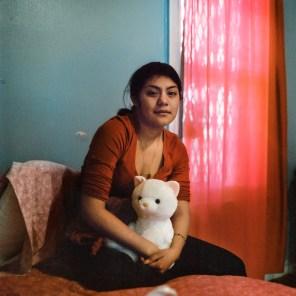 """Delia Guzmán, de 19 años sentada en su cama con su peluche preferido, al que llama """"gatooso"""". Foto: Ruth Prieto"""