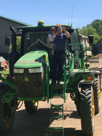 Brother John coming back from spreading fertilizer, holding his daughter