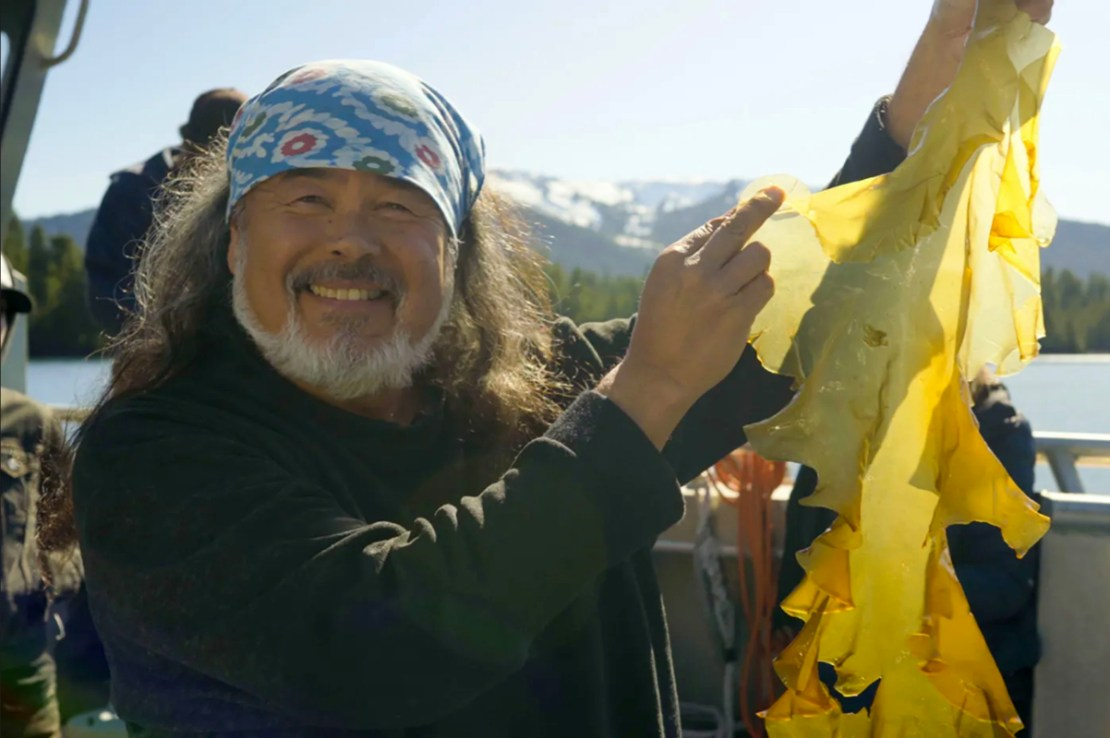 Dune Lankard holding a large piece of sugar kelp grown at one of the seven Native Conservancy test sites in Prince William Sound. (Photo by Ayse Gursoz)
