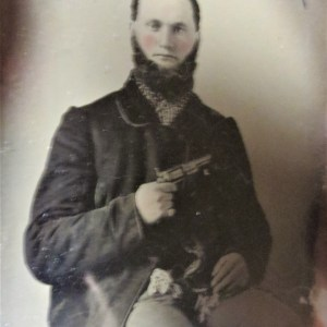 Old picture of a man holding a gun