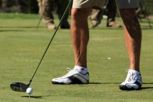 man preparing to hit a golf ball