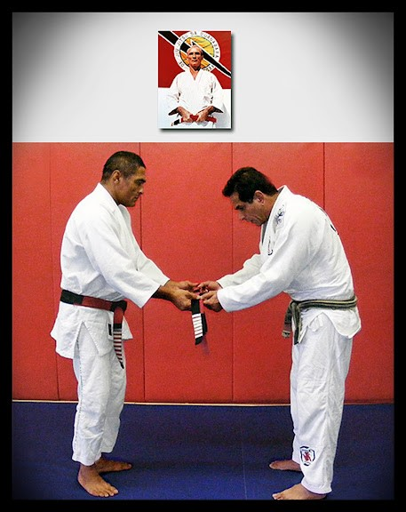 """alt=""""Rickson Gracie presents Caique with the coveted red and black belt"""""""