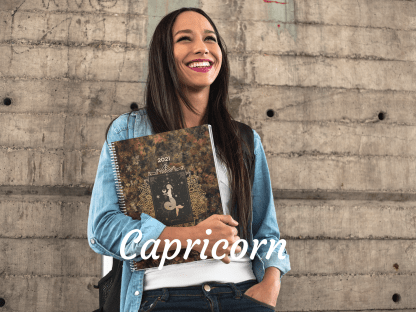 Woman standing in front of dark grey textued wall wearing blue shirt and holding a black and gold Capricorn planner