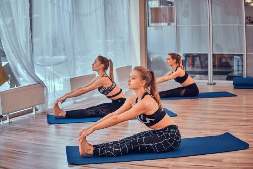Girls are enjoying pilates together at bright room