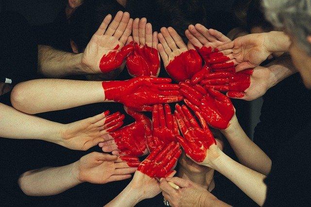 kilka par dłoni z wymalowanym na czerwono sercem