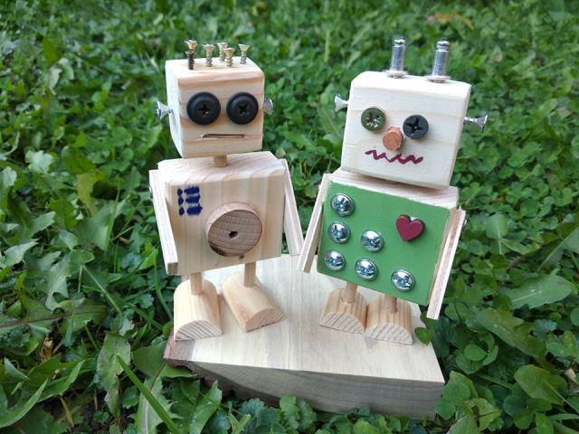 dwa drewniane roboty na trawie
