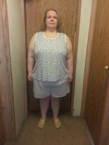 front view of Sarah standing in front of door