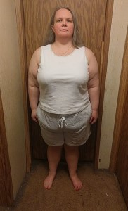 Sarah standing in front of a door wearing shorts and a tank top