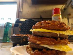 chaffle sandwich on a plate sitting in front of a waffle maker