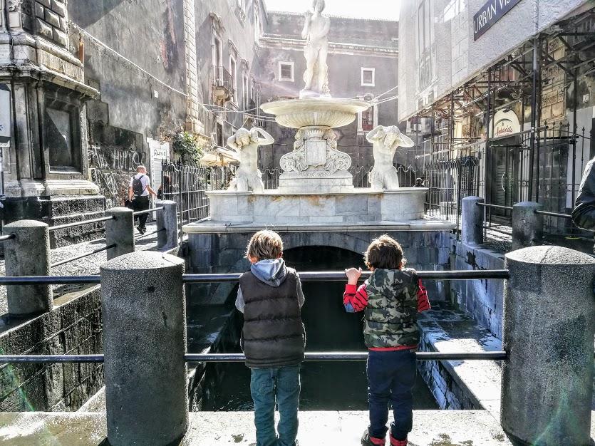dei bambini che guardano la fontana dell'Amenano a Catania