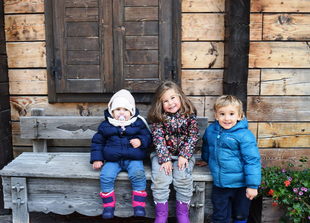 bambini seduti su una panchina a Sappada