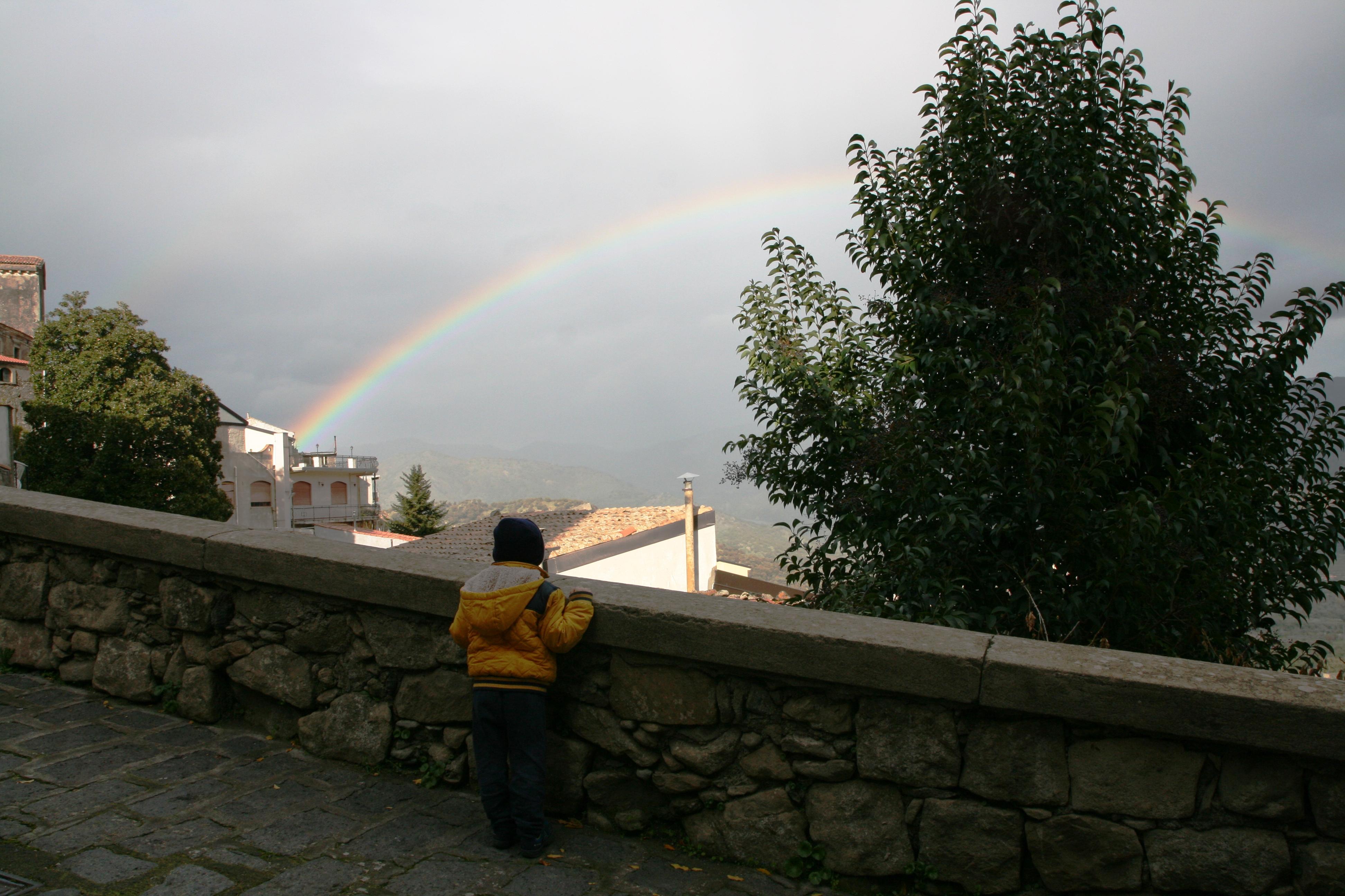 bambino che guarda l'arcobaleno a castiglione di sicilia durante un weekend
