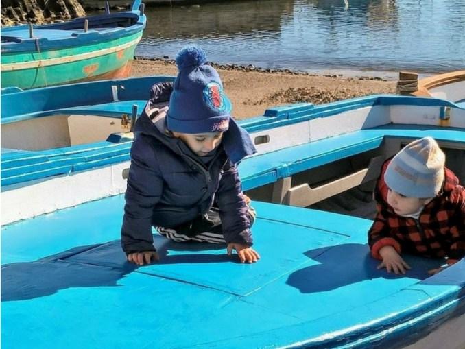 bambini su un'imbarcazione di Aci Trezza
