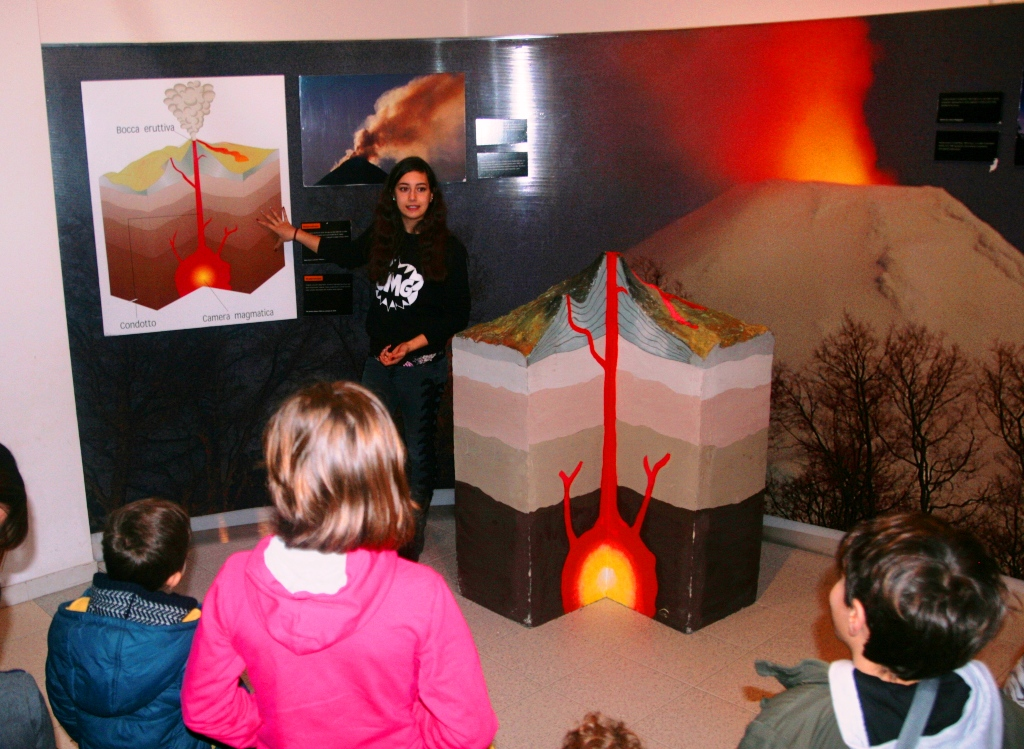 guida che mostra un modello di un vulcano al museo della lava
