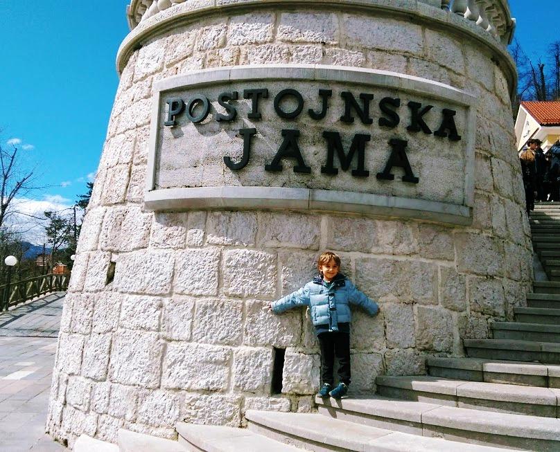 bambino davanti l'ingresso delle Grotte di Postumia