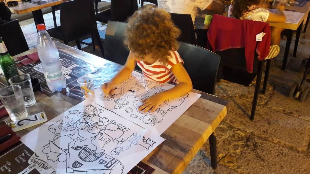 bambina che colora in un ristorante a Castellammare dell Golfo