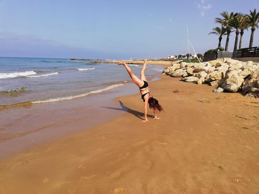 donna che fa una capriola sulla spiaggia a Donnalucata