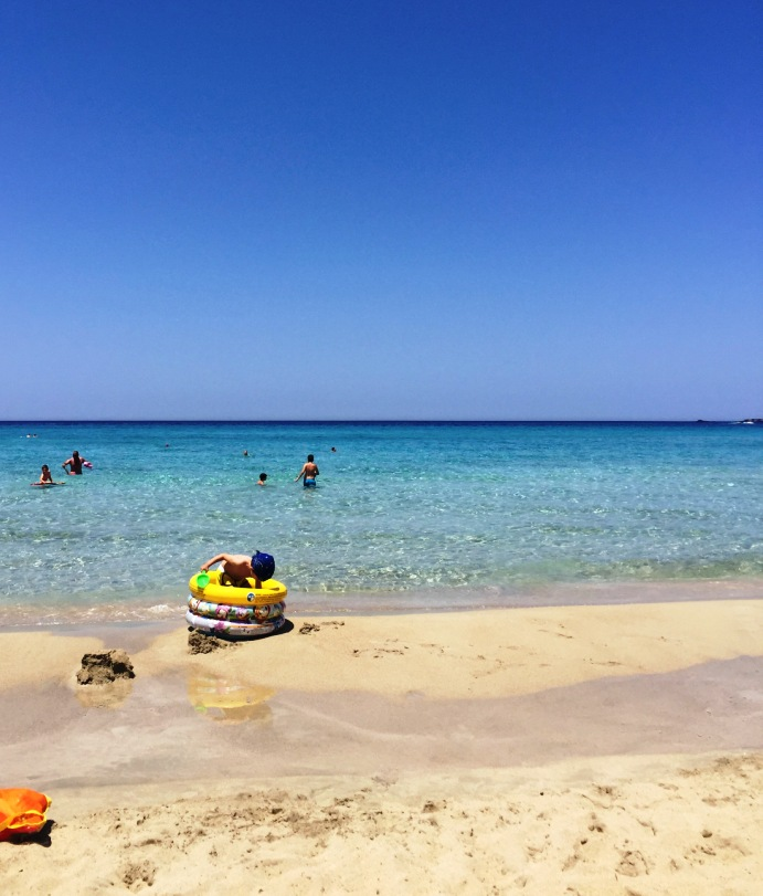 una bambino che gioca sulla spiaggia a Creta