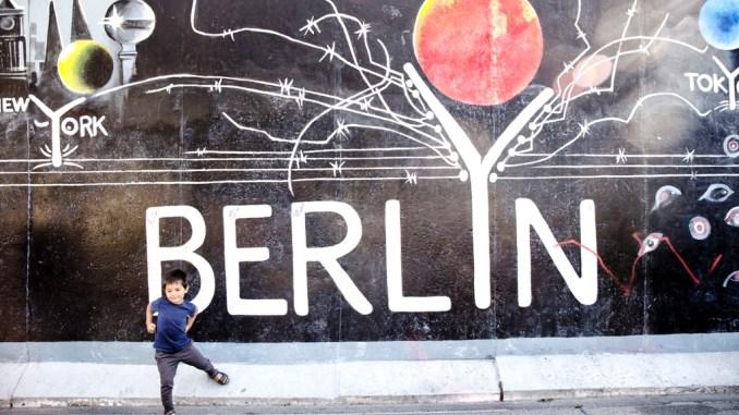 un bambino davanti un murales a Berlino
