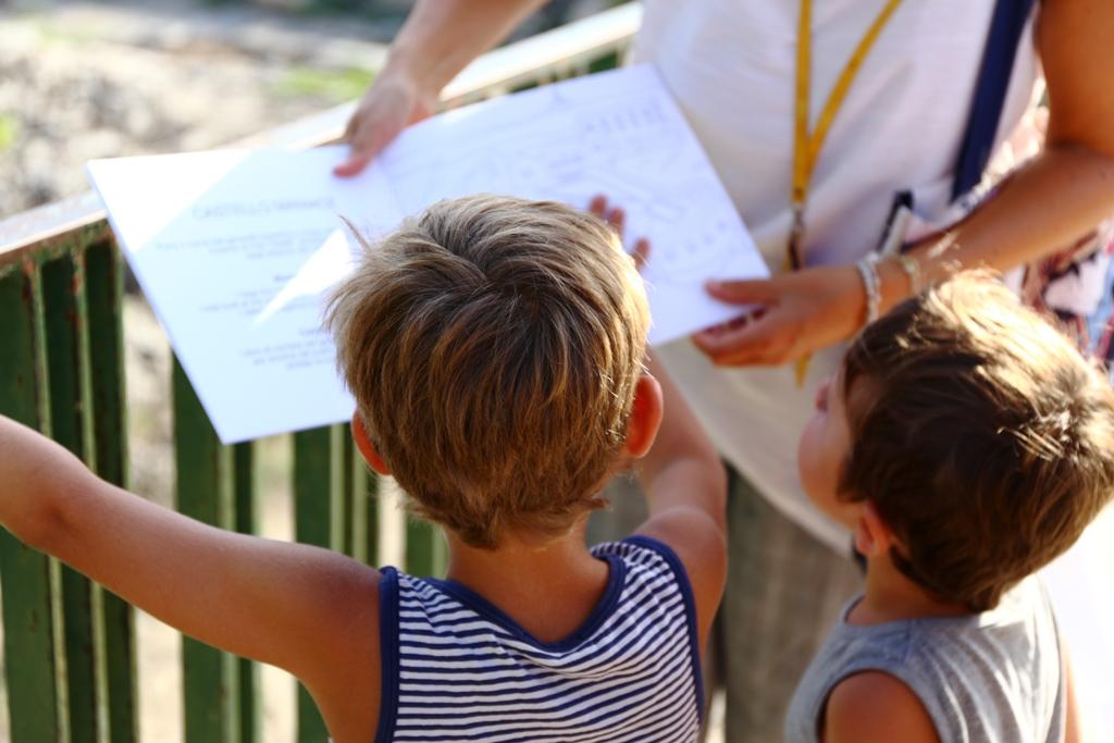 bambini che guardano un libro al Parco Archeologico della Neapolis di Siracusa