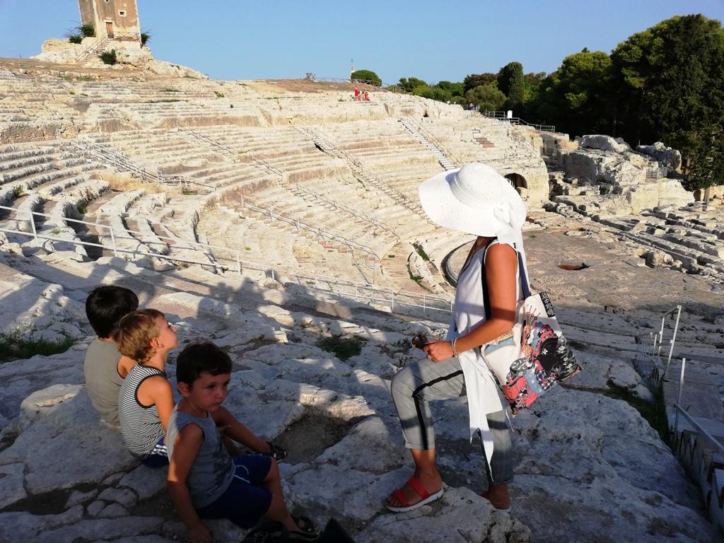 guida turistica con dei bambini al parco archeologico di siracusa