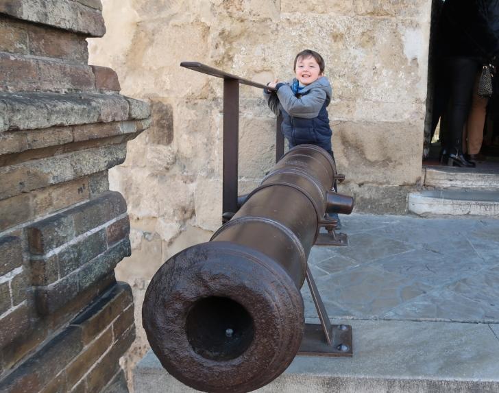 un bambino che gioca con un cannone davanti la Torre del oro di Siviglia