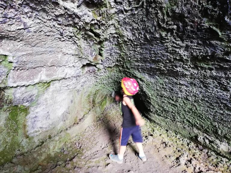 un enfatnt dans un tunnel del lave sur l'Etna