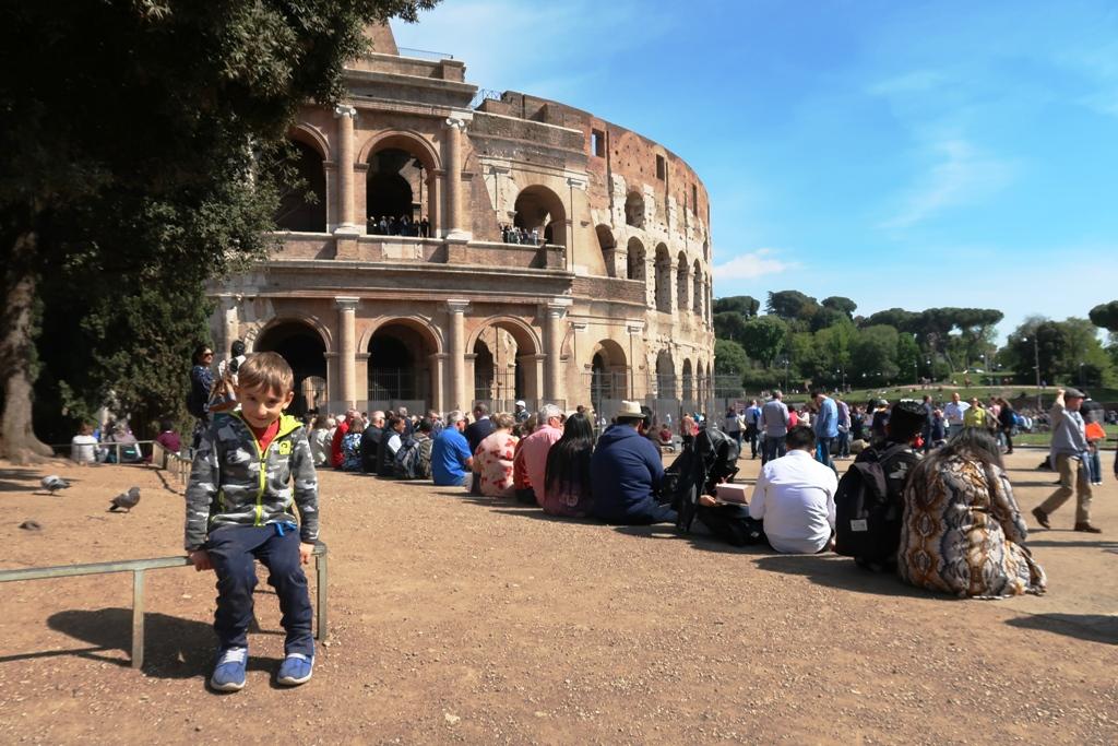 un bambino davanti al colosseo di Roma