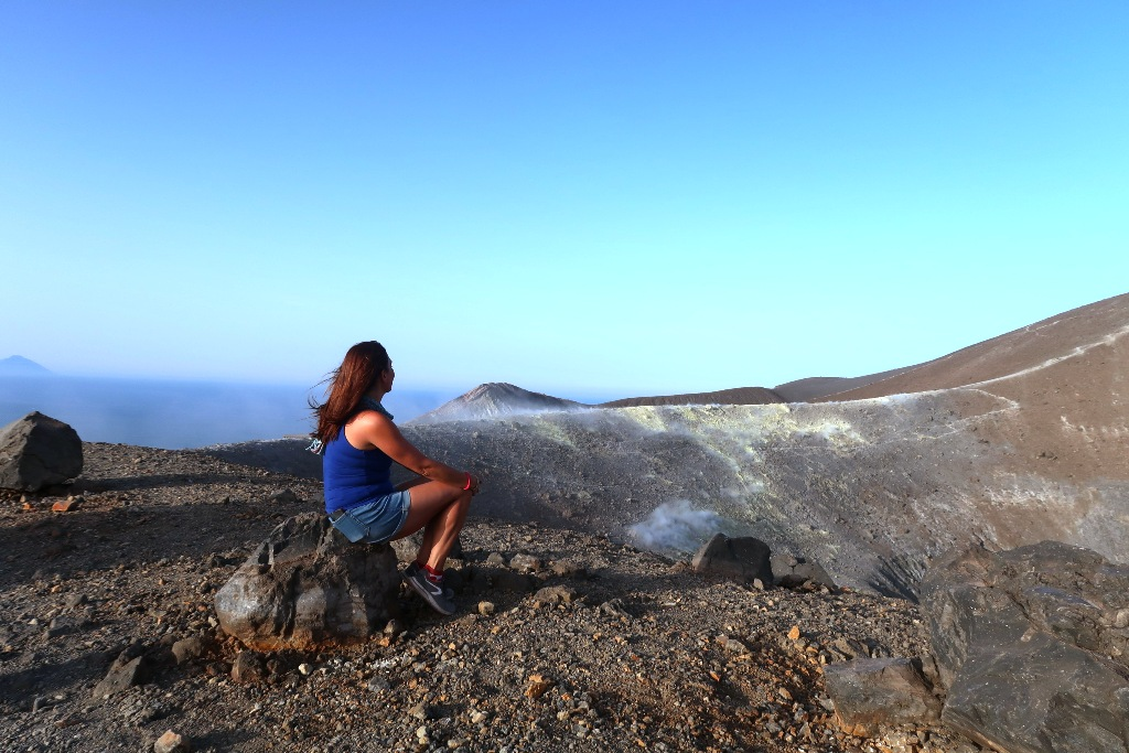 donna che guarda il gran cratere di vulcano
