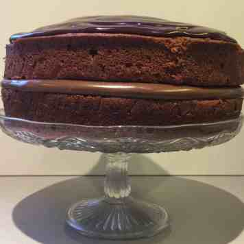 Chocolate Cake with Lindt Hazelnut chocolate spread filling on a glass cake stand