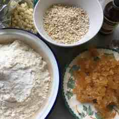 Bowls containing ingredients for ginger, oat and white chocolate cookie bars