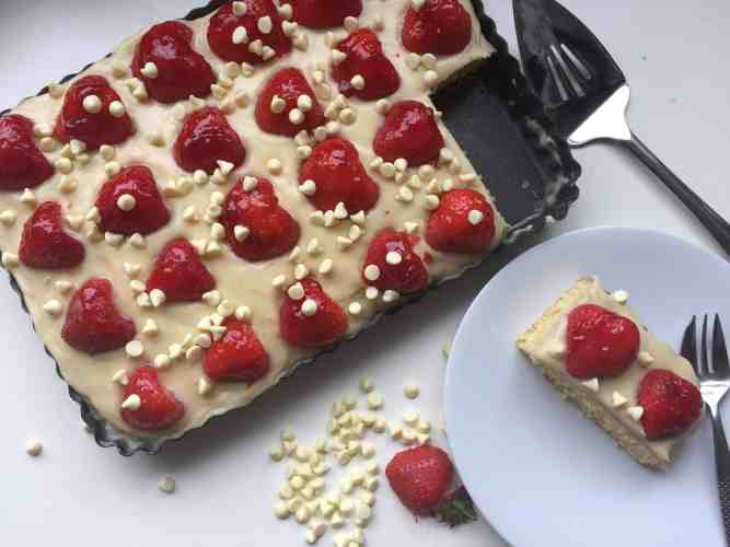 overhead shot of vanilla sheet cake topped with a white chocolate frosting and fresh strawberries , fresh strawberries and white chocolate chips.