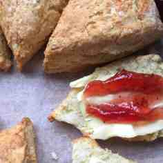 A round of baked scones. One sliced with butter and jam.