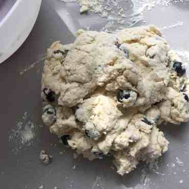 Blueberry scone dough roughly brought together on a counter top.
