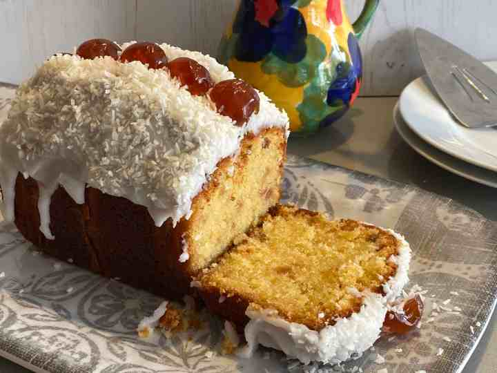 Cherry and Coconut Cake with a slice cut out.