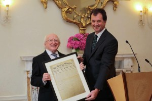 President Michael D Higgins being presented with a copy of The Clare Champion front page of April 1941, when he was born. Photograph by Conor McCabe Photography.