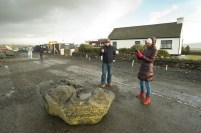 Passers-by take photos of a stray rock on the road at Doolin pier following the storm. Photograph by John Kelly.